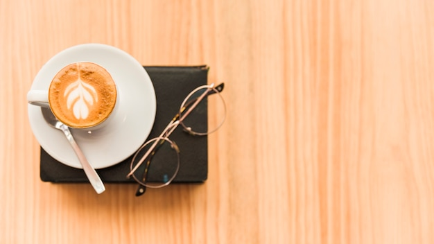 Elevated view of coffee latte and spectacles over book on wooden background