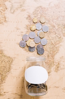 Elevated view of coins over the open jar on world map