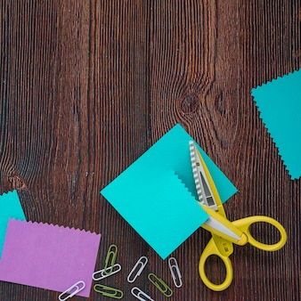 Elevated view of colored papers; paper clips and scissor on wooden desk