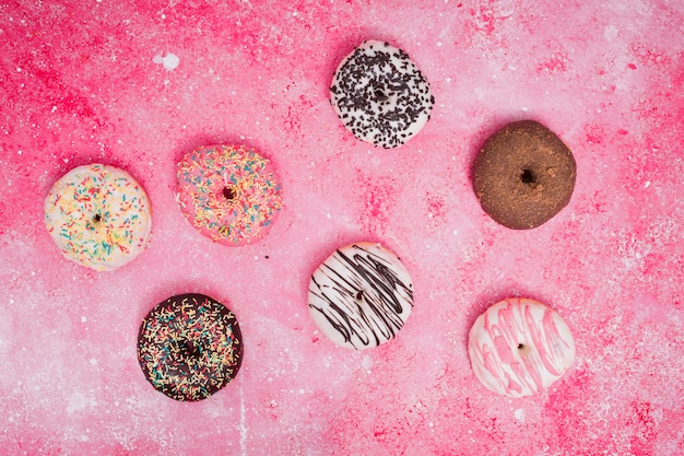 An elevated view of colorful baked donuts on pink background
