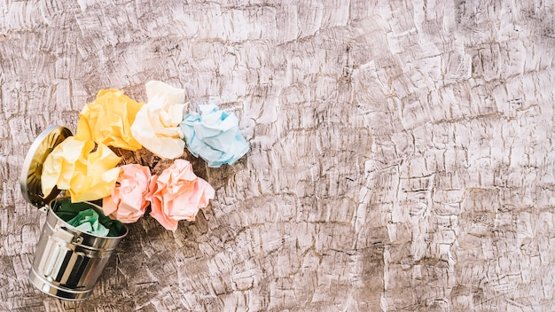 Elevated view of colorful crumpled paper over dustbin on wooden background