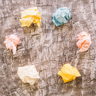 Elevated view of colorful crumpled paper on wooden background
