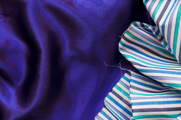 Elevated view of colorful fabric material on smooth purple textile