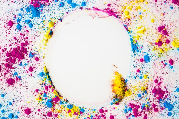 Elevated view of colorful face powder forming circular frame on white surface