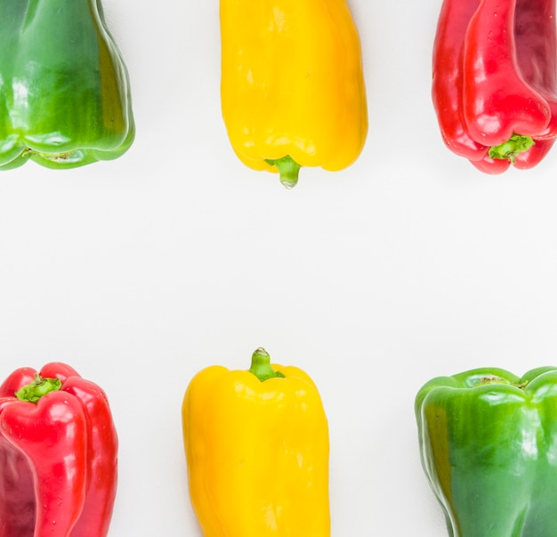 Elevated view of colorful fresh bell peppers on white backdrop