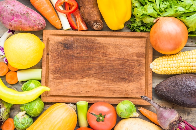 Elevated view of colorful fresh vegetables surrounding wooden chopping board