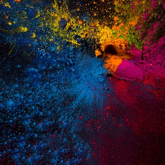 Elevated view of colorful holi powders on black backdrop