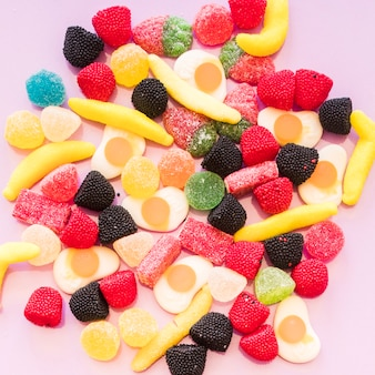 Elevated view of colorful jelly and gummy sugar candies on pink background