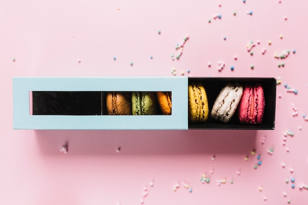 Elevated view of colorful macaroons in a box on pink background