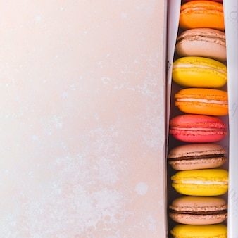 An elevated view of colorful macaroons in box on textured backdrop