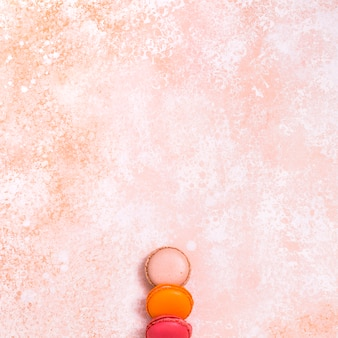 An elevated view of colorful macaroons on rustic textured backdrop
