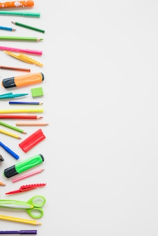 Elevated view of colorful school accessories on white backdrop