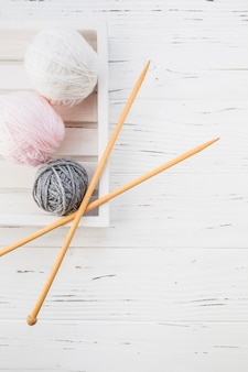 Elevated view of colorful yarns and crochet on wooden background