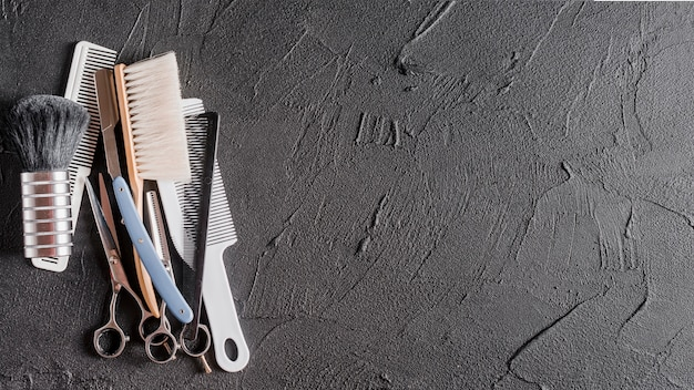 Elevated view of combs, scissors and razor on black surface
