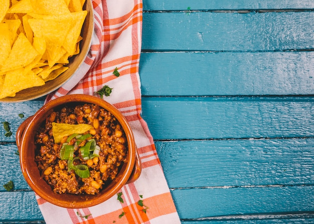 Elevated view of cooked ground beef in bowl with mexican nachos chips on blue wooden desk
