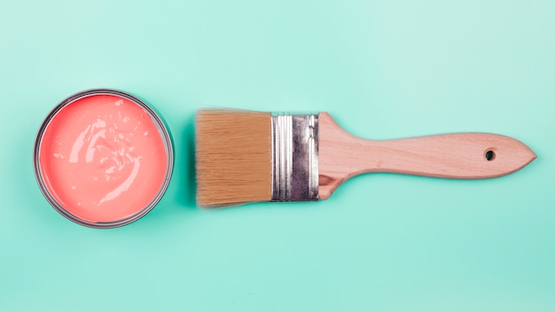 An elevated view of coral paint bucket and paintbrush on mint background