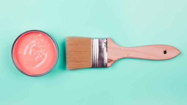 珊瑚油漆桶高架看法和油漆刷在薄荷的背景
