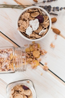 Elevated view of cornflakes in bowl and spilled jar of granola on wooden background
