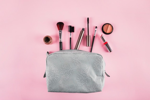 Elevated view of cosmetic bag containing lipstick; mascara; eyeliner and brushes on pink background