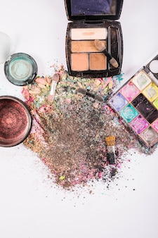 Elevated view of cosmetic powders and brushes on white backdrop