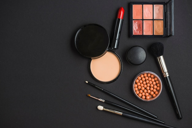 Elevated view of cosmetic products and brushes on black background