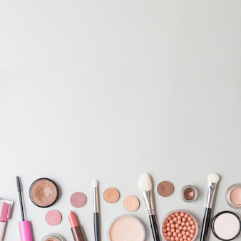 Elevated view of cosmetic products and brushes on white background