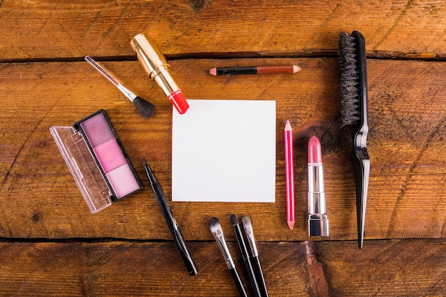 Elevated view of cosmetic products with hairbrush and blank paper on wooden background