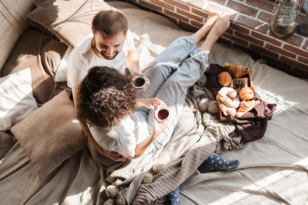An elevated view of couple sitting on bed holding coffee cup
