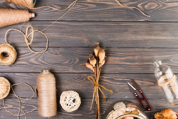 Elevated view of craft material with tied poppy pods and glass bottle