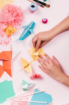 Elevated view of craftswoman making craft with origami paper