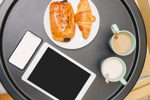 Elevated view of croissants, milk, tea and electronic gadgets on table