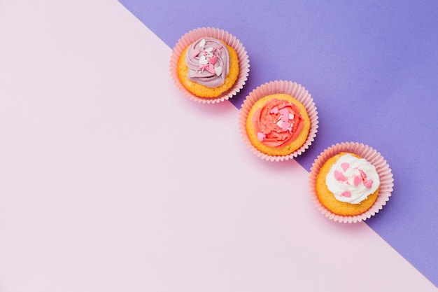 An elevated view of decorative cupcakes on the purple and pink dual background