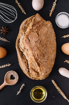 Elevated view of delicious bread with various baking ingredients and utensils on black surface