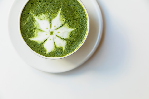 An elevated view of delicious matcha latte flower art cup on saucer over white background