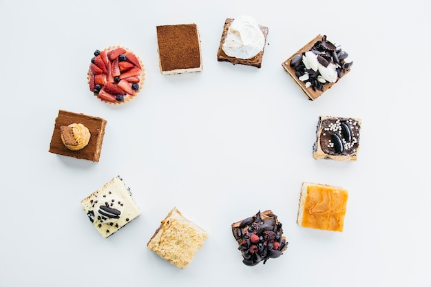 Elevated view of delicious pastries forming frame on white background