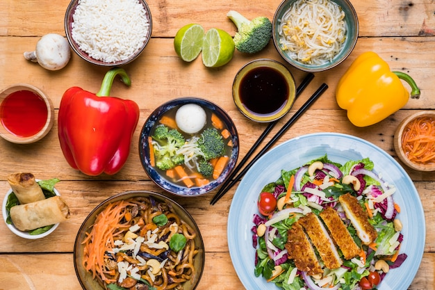 An elevated view of delicious thai food with fresh vegetables on wooden table