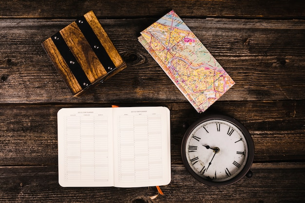 Elevated view of diary, map and clock on wooden background
