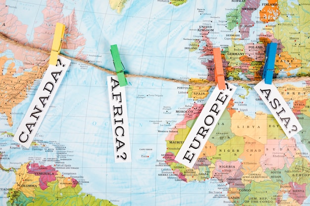 Elevated view of different continent names tag with clothes peg on map