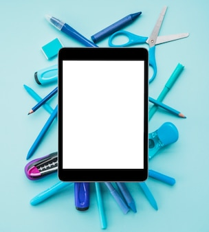 Elevated view of digital tablet on blue stationery over blue color background