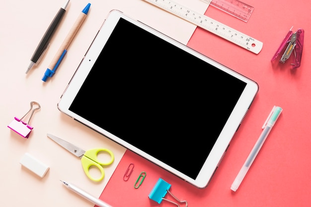 Elevated view of digital tablet surrounded by various stationeries on colorful background