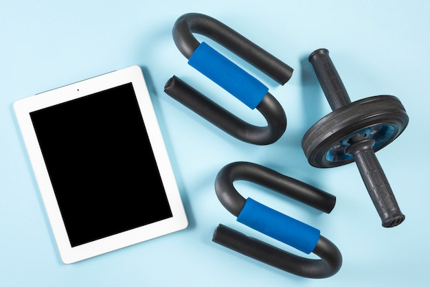 An elevated view of digital tablet with fitness roller and push up bar on blue background