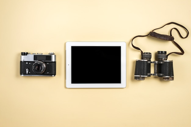 An elevated view of digital tablet with retro camera and binocular on beige background