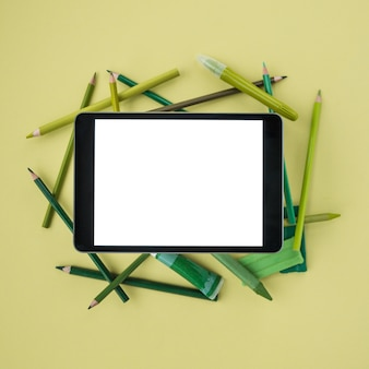 Elevated view of digital tablet with white screen on painting accessories over plain colored surface