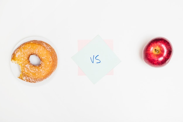 Elevated view of donut versus apple on white surface