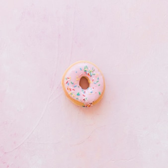 Elevated view of donut with sprinkles on pink backdrop