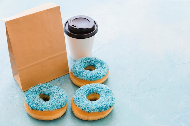 Elevated view of donuts; package and disposal cup on blue background