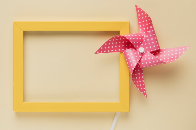 Elevated view of dotted pinwheel and yellow frame on beige background