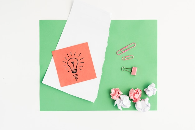 Elevated view of drawn light bulb and crumpled paper with paper clip on green card paper