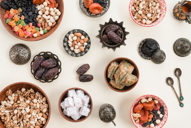 An elevated view of dried fruits; nuts; dates; lukum and baklava bowls over the white backdrop