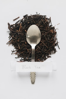 Elevated view of dry black tea leaves with white label on white backdrop
